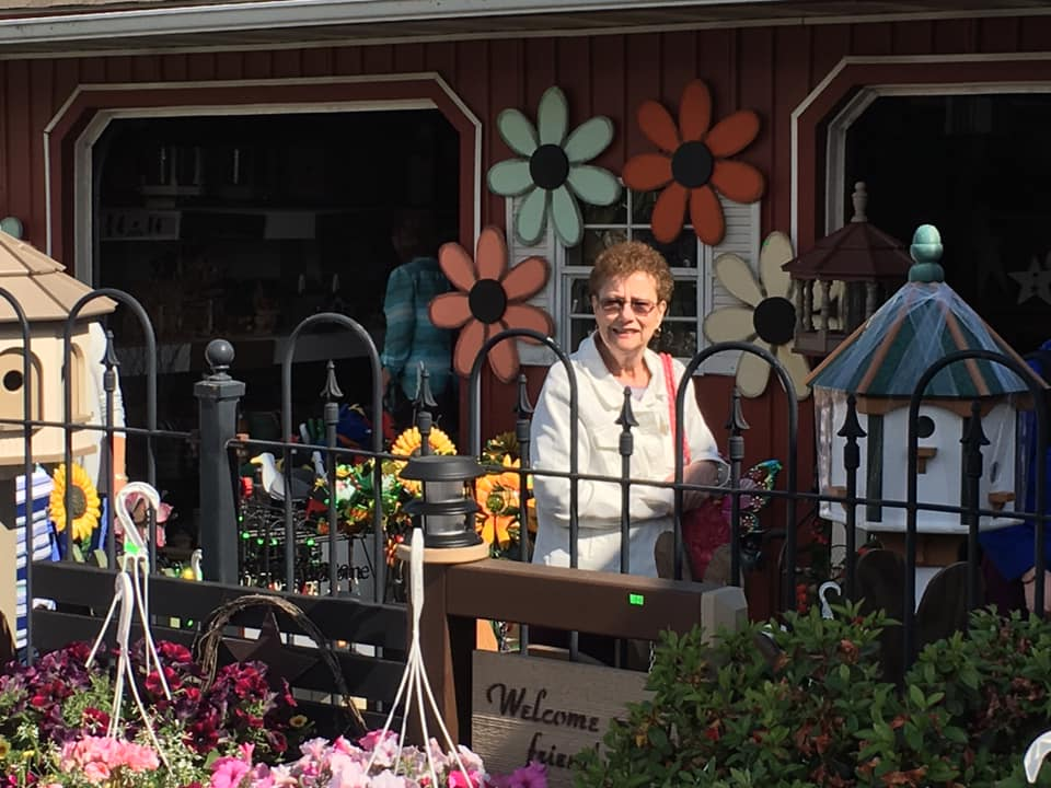 Amish Country Trip Guest, Vicki Smith. A Woman standing outside of a flower shop.